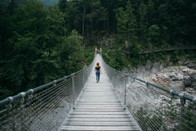 Female Blogger Or Tourist Traveller Walks On Hanging Bridge In Middle Of Mountain Forest, Explores Nature In Natural Surroundings, Peace And Quiet Camping Lifestyle, Travel Destination