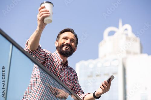 Joyful handsome man dringking tasty coffee outdoors