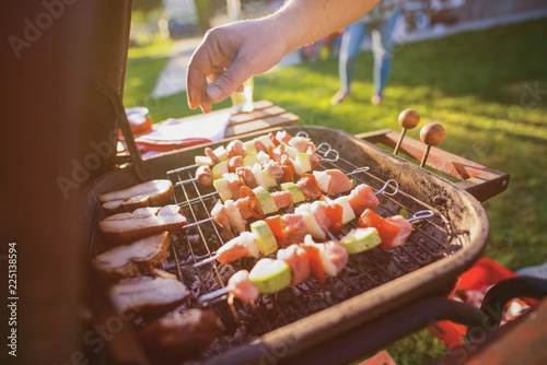 Close up of males hand turning meat and vegetable on barbeque grill.