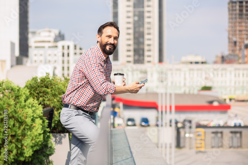 Fotografía  Cheerful adult man standing on the rooftop