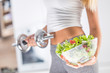 Woman holding bowl from fresh vegetable salad and dumbbell.