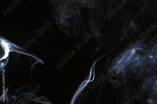 Fotobehang Rook wonderful swirl contrast blue smoke against dark background.