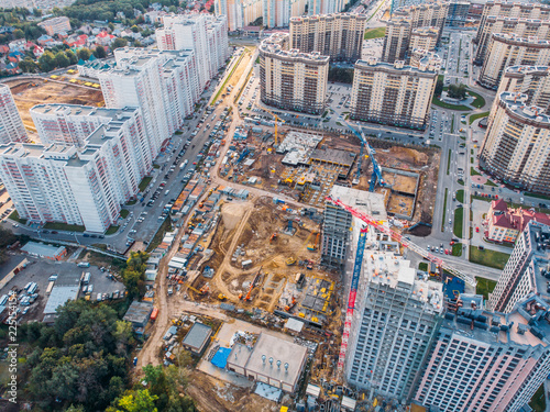 Fototapeta Aerial view from above, construction of modern houses or buildings with cranes and other industrial vehicles among city architecture obraz na płótnie