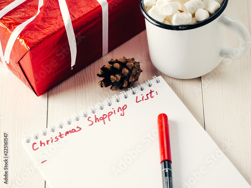 Christmas gifts shopping planning. Make shopping or to-do list for Christmas. Notebook, mug hot chocolate with marshmallows, New Year's gift and pine cone on white wooden background.