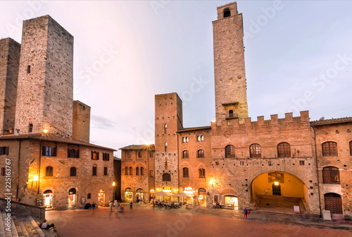 Staande foto Mediterraans Europa Towers and traditional houses on square of ancient Tuscan town in evening lights