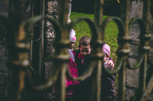 Three Siblings, Small Children At The Old Gate In The Autumn Park