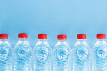 Row Of Plastic Water Bottles With Red Caps Isolated On Blue Background, Copy Space For Text