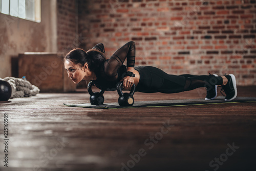 фотографія Fit female doing intense core workout in gym