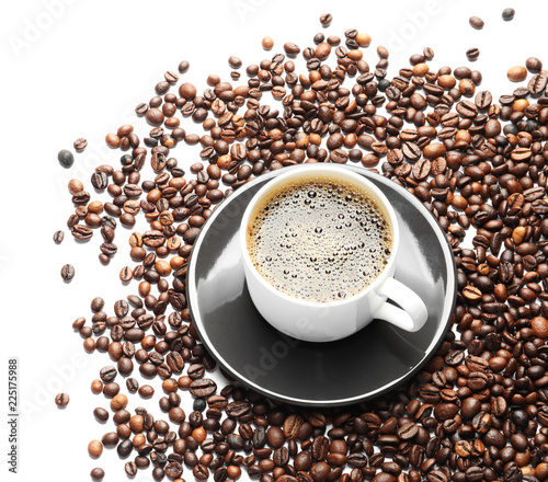 Roasted coffee beans and cup of hot beverage on white background