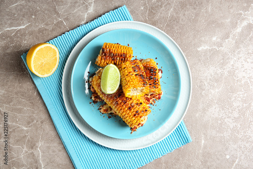 Fotobehang Aromatische Plate with delicious grilled corn cobs and spices on table, top view