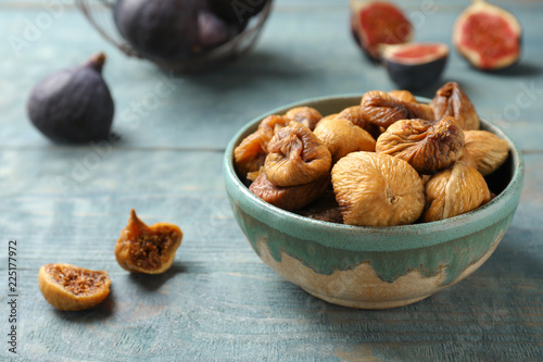 Bowl with delicious dried figs on wooden table. Organic snack