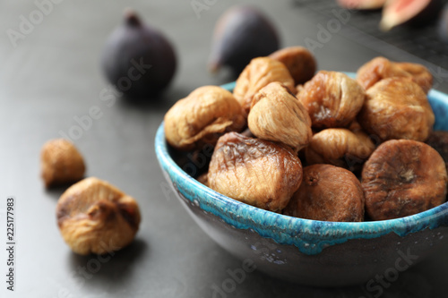 Bowl with delicious dried figs on grey table, closeup. Organic snack