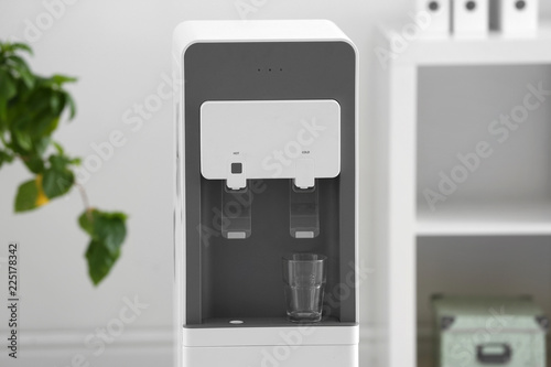 Modern water cooler with glass against blurred background
