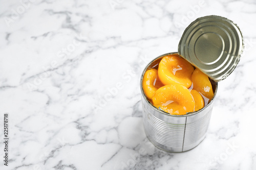 Tin can with conserved peach halves on marble background. Space for text