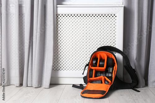 Bag with digital camera on floor indoors. Professional photographer's equipment