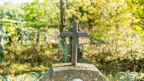 Fotobehang Begraafplaats cross on tombstone, green trees background, cemetery