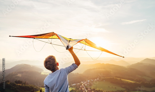 Boy takes a kite over his head. Dreams about flying Canvas Print