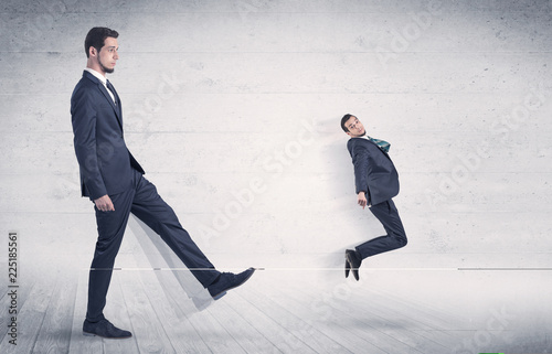 Fotografía  Giant man kicking out small man from space with grungy background