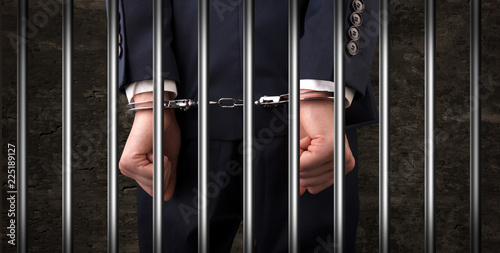Staande foto Hoogte schaal Close convicted man with handcuffs behind grids