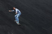 A Man Rolls On A Snow Skateboard From A Black Hill In The Summer