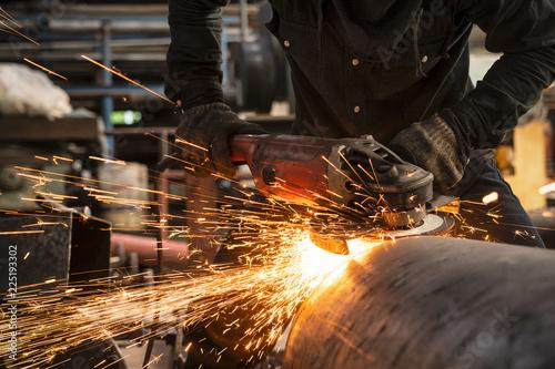Fotografia Electric wheel grinding on steel structure in workshop