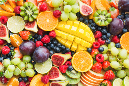 Assortment of healthy raw fruits and berries platter background, strawberries raspberries oranges plums apples kiwis grapes blueberries, mango, top view, selective focus - 225193597