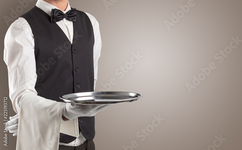 Fototapeta Waiter serving with white gloves and steel tray in an empty space