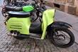 Grüner Motorroller und grünes Moped auf grauem Kopfsteinpflaster
