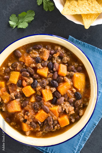 Homemade chili con carne with mincemeat, red and black beans, tomato sauce and pumpkin with tortilla chips on the side, photographed overhead on slate (Selective Focus on the chili)