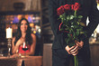 canvas print picture - Romantic surprise concept - a man holding a bouquet of roses and wants to give it to a woman during dinner at a restaurant.