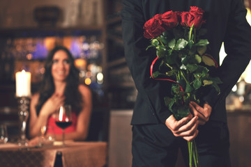Romantic surprise concept - a man holding a bouquet of roses and wants to give it to a woman during dinner at a restaurant.