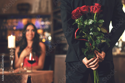 Valokuva Romantic surprise concept - a man holding a bouquet of roses and wants to give it to a woman during dinner at a restaurant
