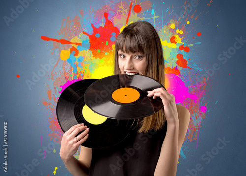 Papiers peints Akt Young lady holding vinyl record on a grey background with colorful splashes behind her