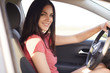 Sideways shot of pleasant looking brunette woman sits in her own automobile, keeps hands on wheel, enjoys high speed, dressed in casual t shirt. Female trainee learns how drive car with instructor