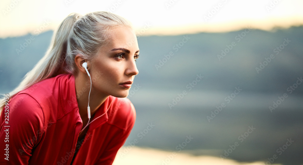 Fototapety, obrazy: Beautiful young woman having rest and listening music outdoors during morning running exercise