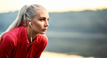 Beautiful Young Woman Having Rest And Listening Music Outdoors During Morning Running Exercise