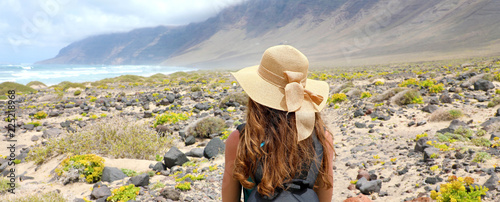 Tuinposter Canarische Eilanden Rear view of traveler girl with straw hat looking at beautiful natural landscape. Young female backpacker exploring Lanzarote, Canary Islands. Banner panorama.