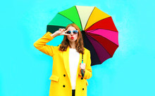 Fashion Portrait Cool Girl Sends Air Kiss With Colorful Umbrella In Yellow Coat Jacket On Blue Background