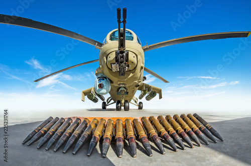 Tuinposter Helicopter Military helicopter is parked, in the foreground the cartridges are the weapons that it shoots.