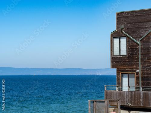 Slika na platnu Modern wooden beachside home overlooks tropical water and sailboat