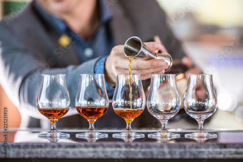 Fotomural Bartender professional preparing five alcololic drinks.