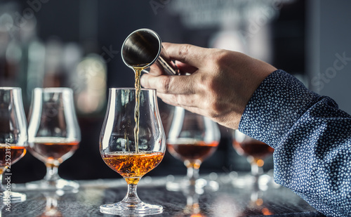 Bartender hand pouring alcoholic drink in nightclub, bar or pub.