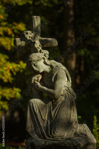 Foto  Sculpture of a Woman kneeling on a Cross - Tombstone on a Cemetery in Berlin, Ge