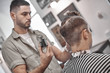 Haircut and hair styling in barbershop. Hair Care. Men's style and lifestyle. Barber brings a haircut and beard to his client.