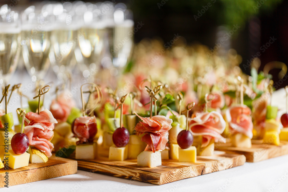 Fototapeta the buffet at the reception. Glasses of wine and champagne. Assortment of canapes on wooden board. Banquet service. catering food, snacks with cheese, jamon, prosciutto and fruit