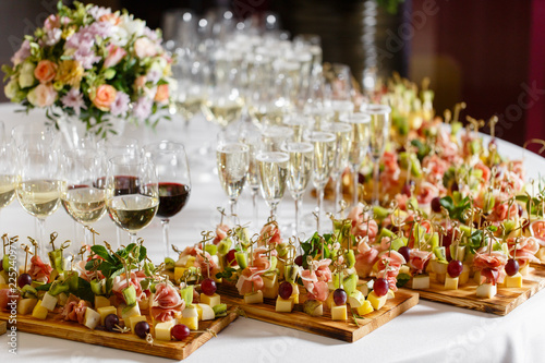 Fototapeta the buffet at the reception. Glasses of wine and champagne. Assortment of canapes on wooden board. Banquet service. catering food, snacks with cheese, jamon, prosciutto and fruit obraz