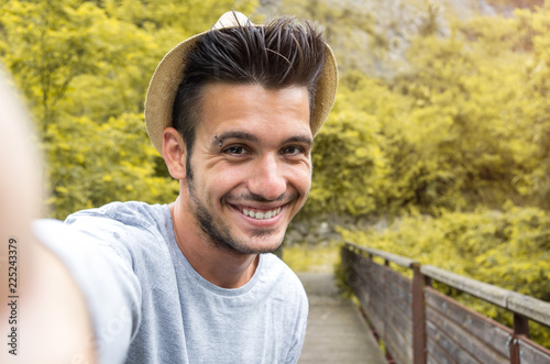 Fotografie, Obraz  Portrait of handsome caucasian man taking a selfie on vacation on a nature backg