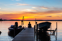 Young Woman Sitting On The End Of A Pier, Watching The Colorful Sunrise. Vacation, Travel, Relaxation Concepts