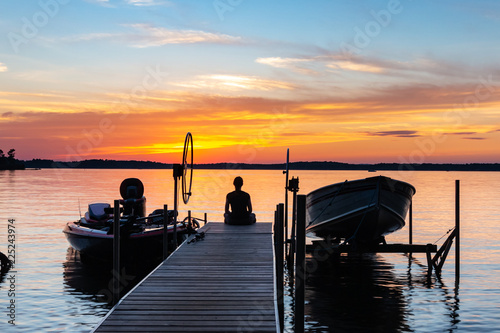 Deurstickers Ochtendgloren Young woman sitting on the end of a pier, watching the colorful sunrise. Vacation, travel, relaxation concepts