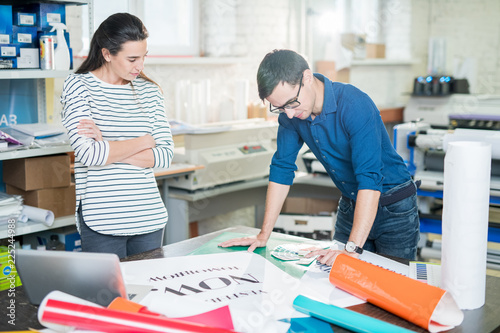 Cuadros en Lienzo  Confident young specialists standing at table full of various types of paper and